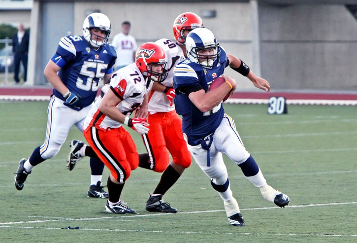 Brandon Leyh of the Langley Rams avoids tackles from Jeffery Mock and Steven Doege of the Okanagan Suns. The Rams lost the Saturday game at McLeod Athletic Park 15-14 to the Suns.