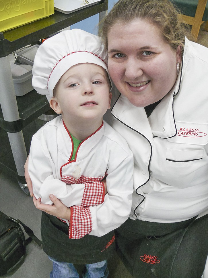 """Lee Holloway, 2, of Abbotsford, was all dressed up in his own chef's uniform to help mom Tamara Sieber with catering a Langley City lunch on Wednesday (March 8). He even had a """"Klassic Catering"""" apron, just like mom."""