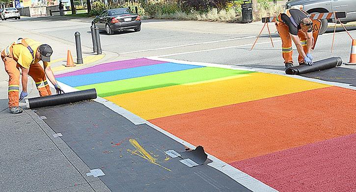 Workers paint a pride crosswalk in Maple Ridge.