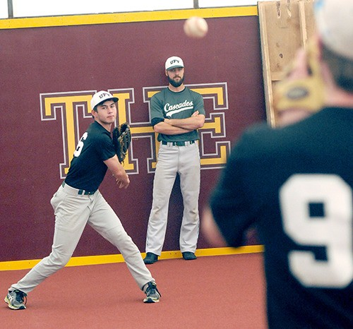 Kyle Lotzkar (middle) watches Cascade outfielder Trevor Brammer throw warm-up tosses during a Tuesday afternoon practice at 'The Yard,' a baseball training facility on Prairie Central Road.