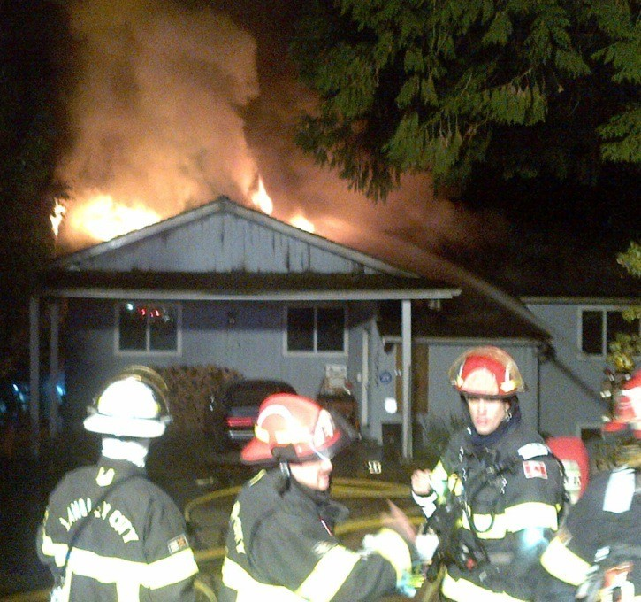 Langley City fire crews battle a fire on Grade Crescent where a 64-year-old woman died on Sunday night.