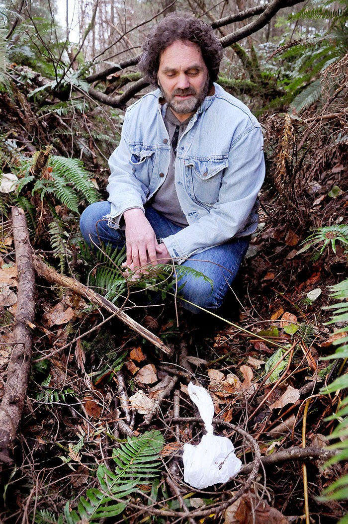 John Freeman kneels near a bag of dog droppings, thrown into a ditch on the side of a trail near Noel Booth Elementary School in Brookswood. Freeman and a friend recently collected 120 discarded bags from the area, only to find the person or people responsible are continuing to dump them.