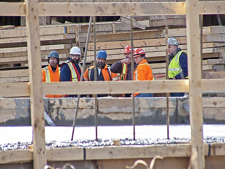 Construction workers survey the scene of an industrial collapse Monday afternoon in a new residential complex being built in the 20200 block of 66 Avenue.