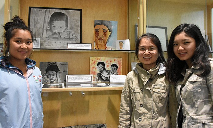 Participants in a refugee art project stand with their work, on display at the Timms Community Centre. From left to right: Moo Doh Paw, Laura Knyaw and Truepayna Moo.