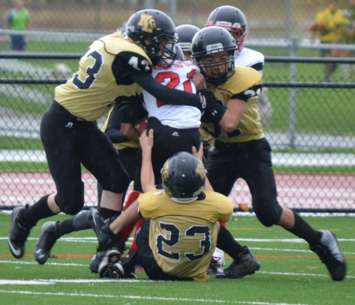 North Langley Bears Brodie Tarling (left to right), Dakota Jenkins and Ethan Bernardin team up to slow an Abbotsford Falcons ball carrier in junior bantam football action.