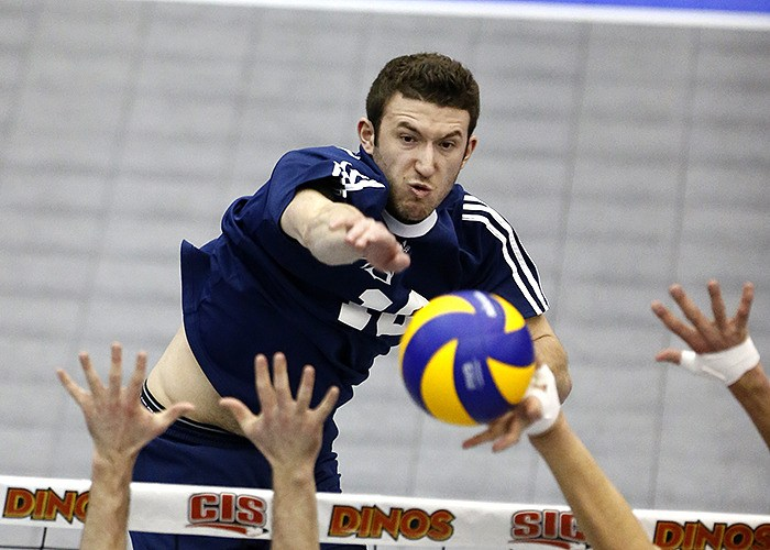 Trinity Western Spartans Branden Schmidt sends the ball past the block of the Western Mustangs during CIS quarter-final action. The Mustangs derailed the Spartans national title dreams with a 3-2 victory in Calgary.
