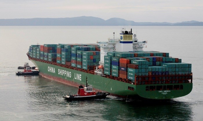 Seaspan tugs shepherd a large container ship inbound to Deltaport.