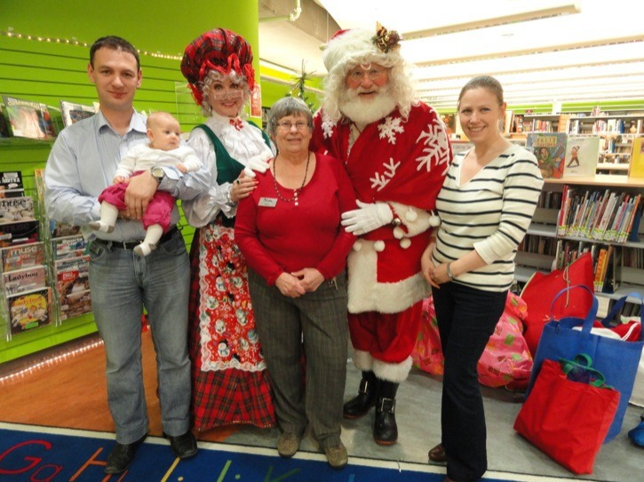 Standing with Mr. and Mrs. Santa Claus is Nancy Bolton, her daughter Jennifer, son-in-law Elie, and granddaughter Aurore (3 months) at the Muriel Arnason Library where the first Christmas fun was held. The event  was a huge success and drew 150 kids and caregivers who took part in singing, stories and getting pictures taken with Santa and Mrs. Claus.
