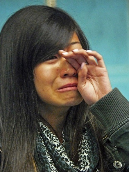 Tracey Phan wipes a tear as she talks to reporters about her father, one of five victims of a mushroom farm gas buildup.