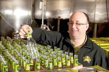 Dead Frog Brewery founder and CEO Derrick Smith inspecting a bottle at the brewery.