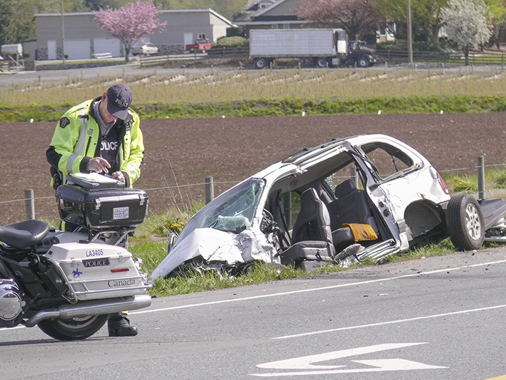 An RCMP accident investigator takes notes at the scene of a fatal crash on 16 Avenue near 224 Street. The driver of the mini-van died after she was involved in a collision with a pickup truck.