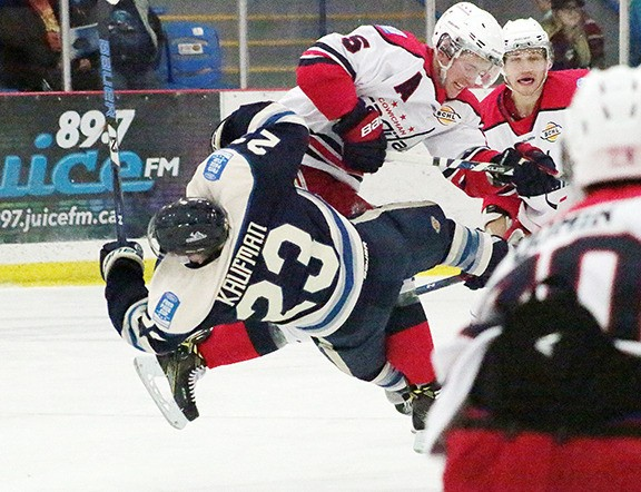 Veteran Capitals defenceman Ben Verrall levels Langley's Max Kaufman with an open-ice hit in the second period of Cowichan's overtime win against the Rivermen on Saturday.