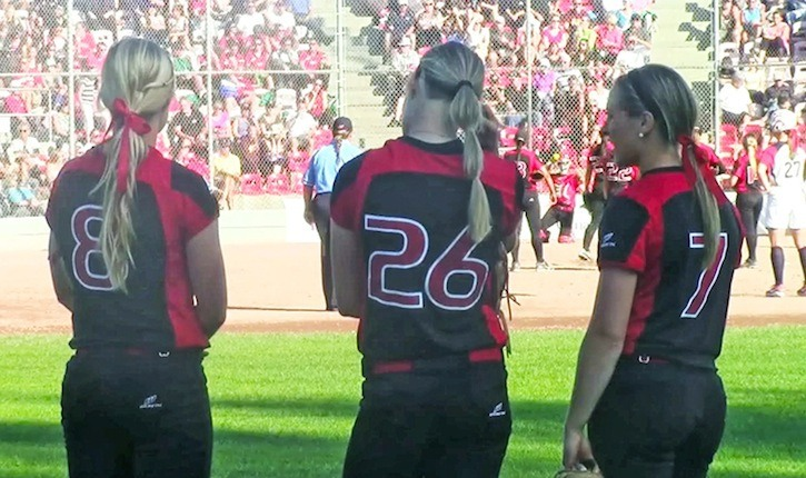 Canadian outfielders Victoria Hayward (#8), Larissa Franklin (#26), and Erika Polidori (#7) watch pitcher Jenna Caira warm up during the third inning of their semifinal game against Team USA. Canada lost 9-2 on Monday night, winning Bronze at the 2014 Canadian Open in Surrey, B.C.