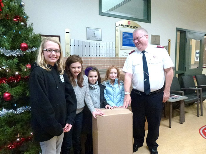 Glenwood Elementary School students (L-R) Emma McDiarmid, Emma Wiebe, Abby Wiebe and Grace McDiarmid brought boxes upon boxes of coats, hoodies, scarves, gloves and more to Gateway of Hope Major James Hagglund who told the girls all of the clothing would go to good use.