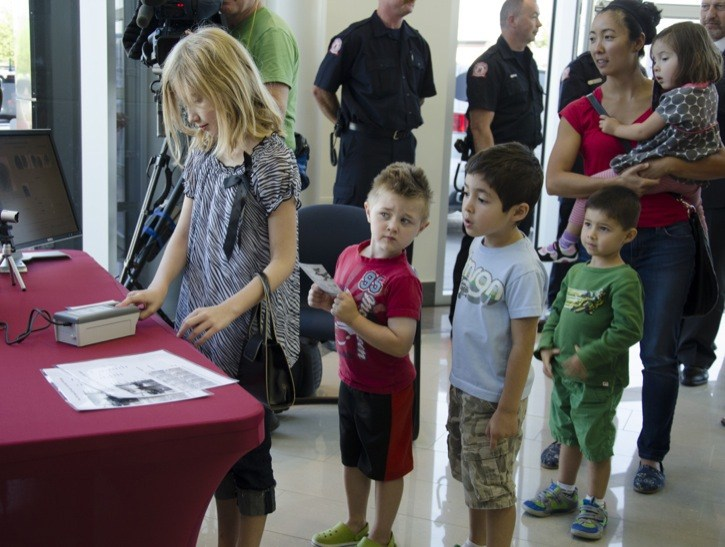 Children line up at the fingerprinting station at Preston GM, following an official ceremony Wednesday, launching the service offered by Operation Kidsafe. Fingerprints are retained by parents for use in case of emergency.