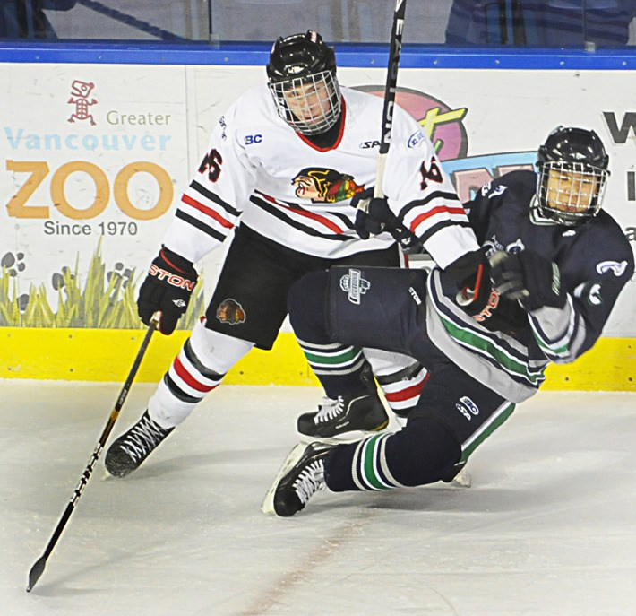 Kevan Kilistoff of the Valley West Hawks (left) sends a South Island Thunderbird to the ice during Saturday's B.C. Major Midget League game at the Langley Events Centre Saturday. The Hawks won 4-1.
