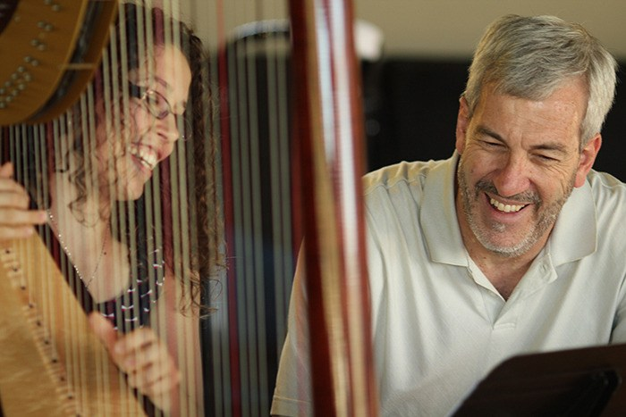 Fourth year TWU harpist Esther Cannon and music department dean David Squires converse about a piece, titled Wave After Wave, which Squires wrote for harp and orchestra.
