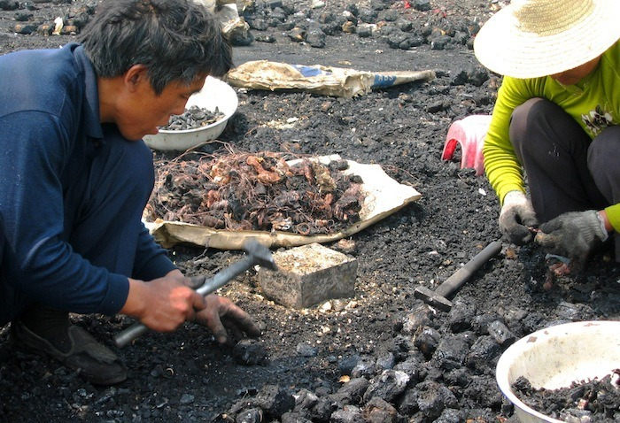 Migrant workers from Hunan and Szechuan provinces cracking open charred components to remove the copper at the burn village near Guiyu, China in 2008.