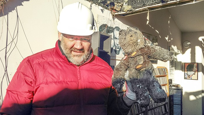 Paddington Station resident Geoffrey Holland found the bear his mother made for him buried underneath a pile of debris when he returned to his burnt-out fourth-floor residence for the first time since the fire; below: Paddington Bear in better days, when a young Holland, shown with his sister, Sarah, received the stuffed animal as a Christmas gift from his mother.