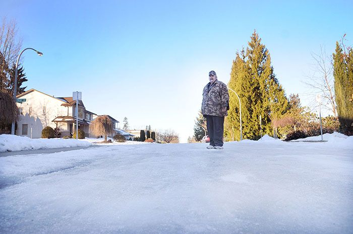 Marvin Braun stands on an ice-covered 98 Avenue in Walnut Grove. He and neighbour Deanna Cindrich are frustrated by the lack of snow and ice removal on their street. The Township prioritizes roads by traffic volume and says once too much ice forms, there is little they can do to melt or remove it.