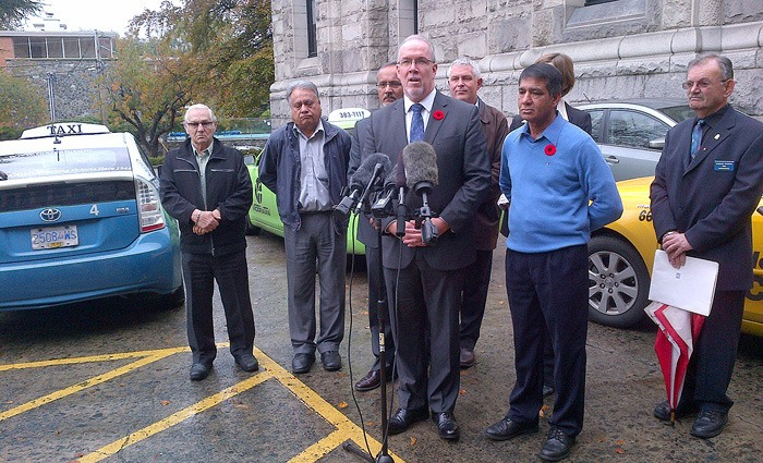 Flanked by taxi drivers and managers, NDP leader John Horgan calls for a huge increase in fines aimed at Uber and other web-based ride services.