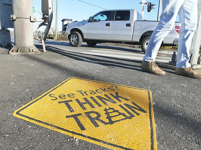 Langley City may be the first Lower Mainland municipality to post ground-level warning signs aimed at people walking and texting. This is one of four signs installed at level railway crossings.