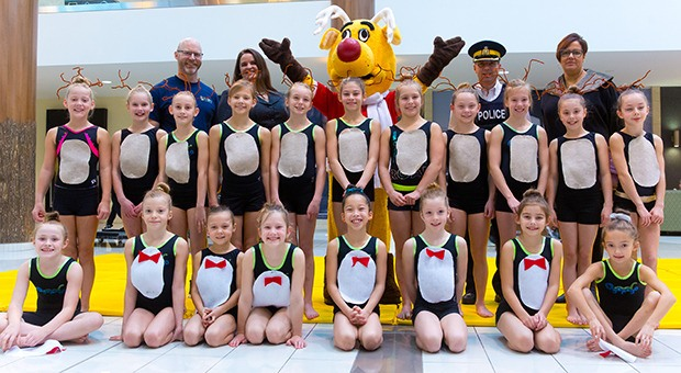 At a launch event at Guildford Town Centre, young members of Langley Gymnastics pose for a photo with (back row, left to right) Mike BIggin, Melissa Coombes, Rudy the Operation Red Nose mascot, RCMP Inspector Andy LeClair and Karen Klein.
