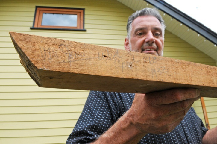 Matt  Choquette shows off a short beam, found on the left side of the attic window at Beatniks Bistro, which is signed by the builder V. W. Jones on April 26, 1933.