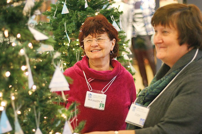 Volunteers Maureen Airey (left) and June Cox (right) man the desk at the Langley Hospice Society memorial Christmas trees at Willowbrook Shopping Centre Tuesday (Dec. 10). It's an opportunity for people to honour the memory of a loved one or pet by writing their name on an ornament and placing it on one of the memorial trees.