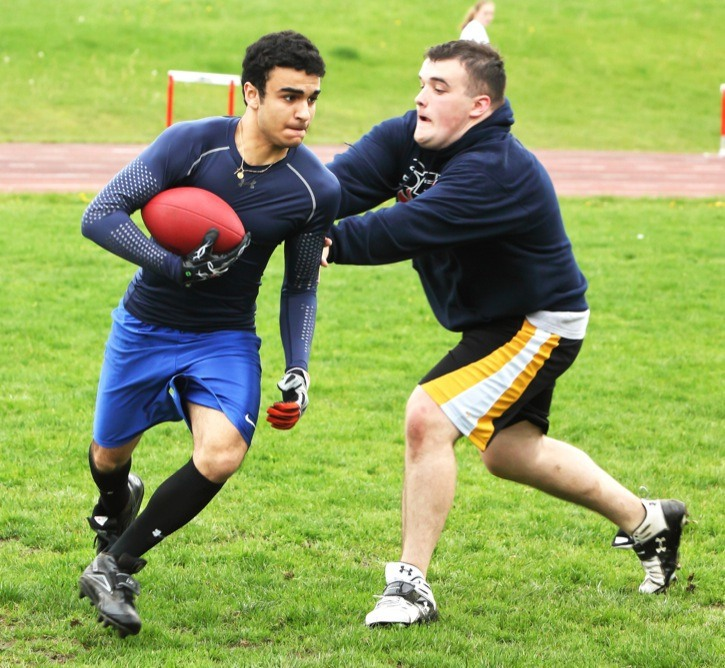 Joe Brake (with ball) is tagged by Keith Horne during a scrimmage at the North Langley Community Football Association skills camp held on Saturday at Walnut Grove Secondary School.