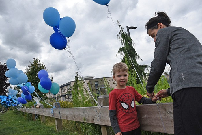 People have begun tying blue balloons to a fence near the Langley townhouse complex where a four-year-old boy died on Thursday, after falling out a third floor window. Gillian and Nate Long came to pay their respects on Friday afternoon. Nate is also four, so 'it really hit close to home for us,' Gillian said. They don't know the family, but saw what happened on Facebook and wanted to show their support.