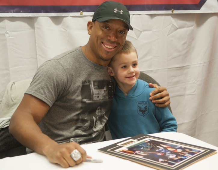 Geroy Simon, aka Superman, poses for a photo with young fan Colten Buckley, 6, during a signing session at Langley's Pastime Sports & Games on Saturday. More than $1,000 was raised for the Men of Hope and the B.C. Society for Male Survivors of Sexual Abuse.