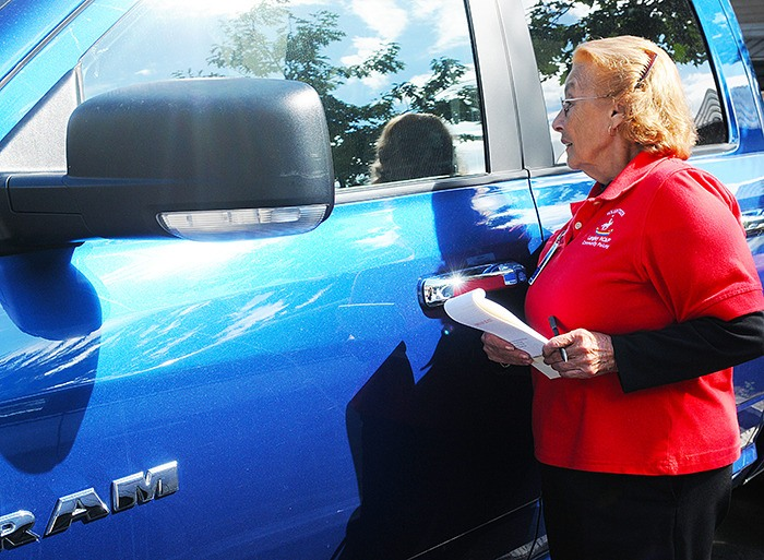 Stella Sandyke, a volunteer at the Brookswood CPO, checks to see if the owner of this vehicle has left valuables in the truck. Sandyke is taking part in the RCMP's Lock Out Auto Crime campaign.