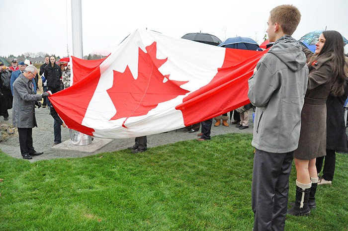 Michael and Elizabeth Pratt are joined by Township of Langley mayor Jack Froese, as well as Langley MP Mark Warawa and Langley MLA Mary Polak (not shown) in raising a giant Canadian flag during a Remembrance Day ceremony held at the Walk to Remember in the Derek Doubleday Arbouretum. Warawa presented the flag which once flew atop the Peace Tower in Ottawa.
