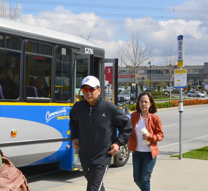 Passengers depart a bus at Grandview Corners Friday, where a sign advises of a news White Rock-Langley service starting April 23.