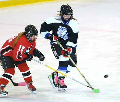 Langley Lightning's Tamara Porter (right) tries to fight through the stick check of her Whistler Hawks opponent during bantam C2 hockey action at the George Preston Recreation Centre on Saturday. The visiting Hawks edged their Langley hosts 3-2.
