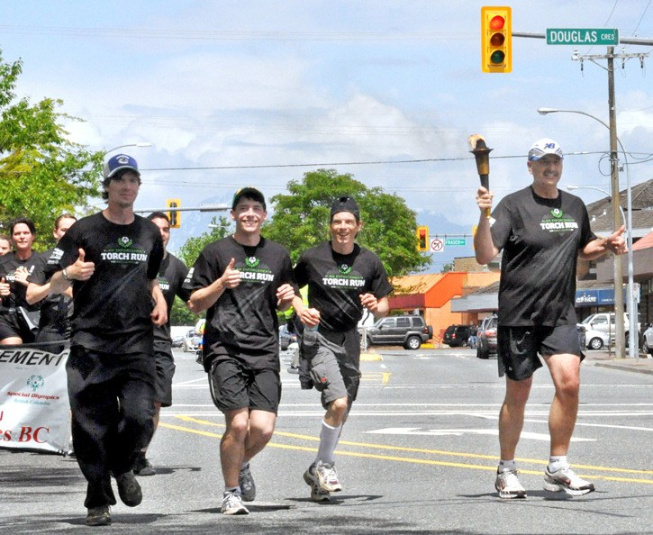 Inspector Richard Konarski, right, carries the torch and leads the Law Enforcement Torch Run alongside three Special Olympics athletes, including  Matthew Williams, second from left, who says the Games have given him the opportunity to meet new people and travel.