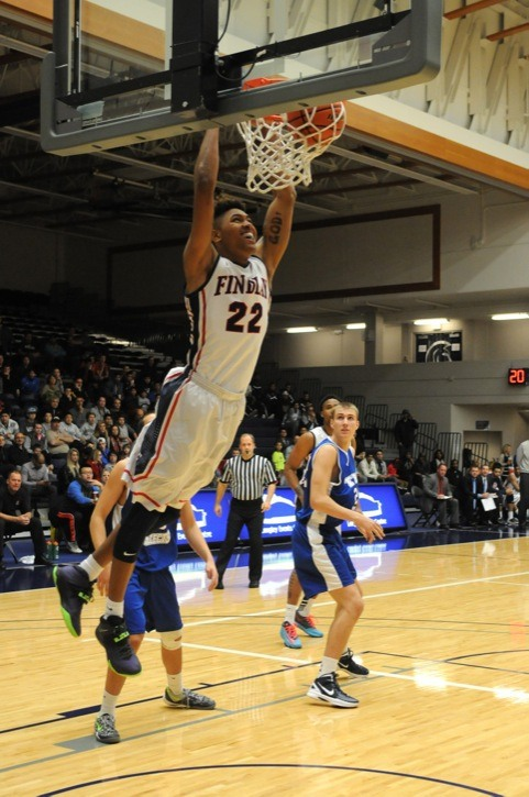 Findlay Prep Pilots' Kelly Oubre — who is off on scholarship to the University of Kansas next season — hangs on the rim after a dunk during his team's game against the TBI all-stars at the Langley Events Centre on Dec. 1.