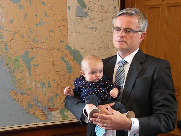 Chilliwack-Hope MLA Barry Penner holds his daughter Fintry, speaking to reporters about his decision to leave the attorney-general's office.
