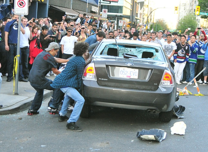 A large crowd records images as a handful of rioters prepare to flip a car at the Vancouver Stanley Cup riot June 15.