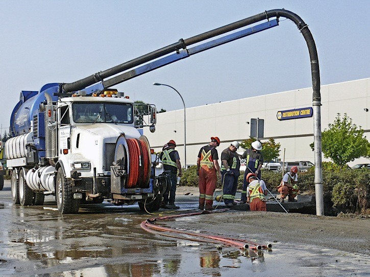 Township crews work on repairing a burst water main on 200 Street Wednesday that caused morning rush hour traffic backups.