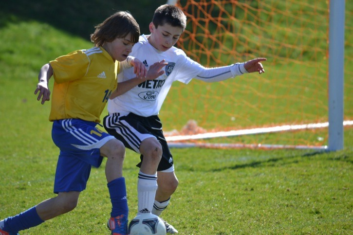 Langley United's Jacob Sol (left) fends off a Coquitlam Metro Ford defender during U12 action at Willoughby Community Park on Saturday. Langley won the game 5-2.
