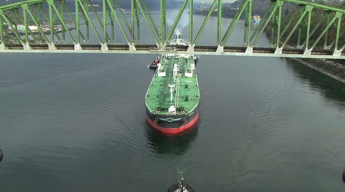 An oil tanker is flanked by tethered tugs as it heads out of Burrard Inlet.