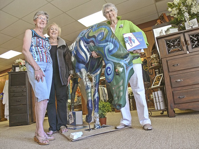 From left Mary Ball (wife of the late Dale Ball) Ella Little and artist Marilyn Dyer pose with Tattoo the horse inside Ella's boutique. The horse sculpture, painted by Dyer, became the subject of a book about bullying after it was twice vandalized in a Brookswood park. The artist, who provided the images to accompany  Summerland author, Ruthie Charles' words, will read from and sign copies of the book during Brookswood Days on Saturday, June 13. The 16th annual event, which runs from 10 a.m. to 3 p.m., will include live entertainment, Scruffles the Clown, balloon art, Madame Butterfly, a jewelry artist, B.C.'s strongest man, Chris Davies, and a number of other merchant events. Visit brookswoodvillage.com for more information.
