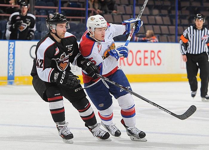 Carter Popoff (left) skates alongside an Edmonton Oil Kings opponent during a WHL game Wednesday in Edmonton.
