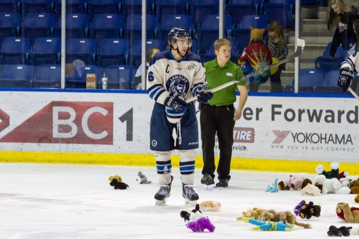 Langley Rivermen captain Kevin Kilistoff helps collect the teddy bears off the ice during the Rivermen's Teddy Bear Toss game two years ago. Fans are encouraged to throw new or gently-used teddy bears to celebrate the team's first goal during their game on Dec. 12 at the Langley Events Centre.