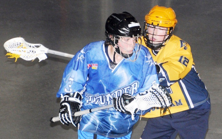 Langley Thunder's Bryce Johannes absorbs a cross-check from Coquitlam Adanacs' Nic Payette during A2 action at the 35th annual Dennis Hickey Lacrosse Tournament over the weekend at the Aldergrove Arena. Langley won this game 6-5 and won the bronze medal.