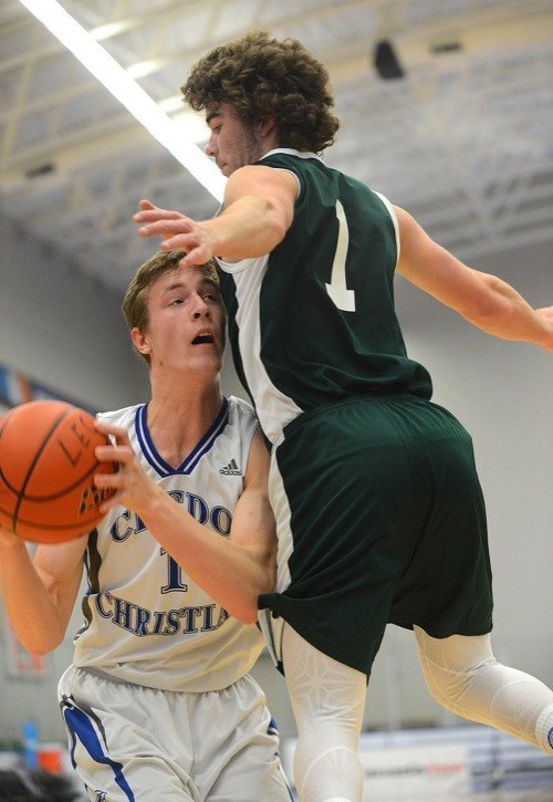 Credo Christian Kodiak Levi Leyenhorst (left) is chest-blocked by Josh Laffin of the Fraser Lake Cougars on the opening day of the 2017 BC High School 1A boys basketball championships at the Langley Events Centre.