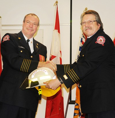 Rory Thompson, left, formally received his fire chief's helmet from acting chief Jim McIntee at a ceremony on Friday.