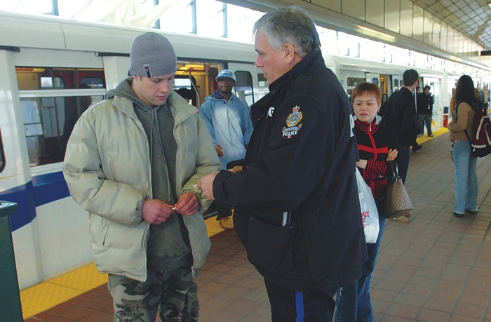 Transit Police officer conducting a fare check at a SkyTrain station.